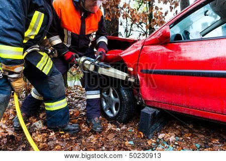 Accident - Fire brigade rescues accident Victim of a car using a hydraulic rescue tool poster