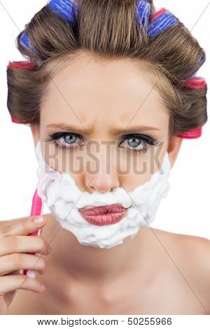 Serious model in hair curlers posing with shaving foam and razor on white background