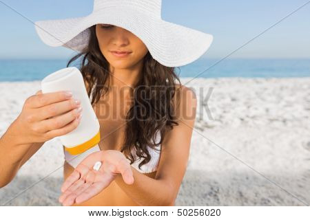 Sexy young brunette on the beach taking care of her body putting on sun cream
