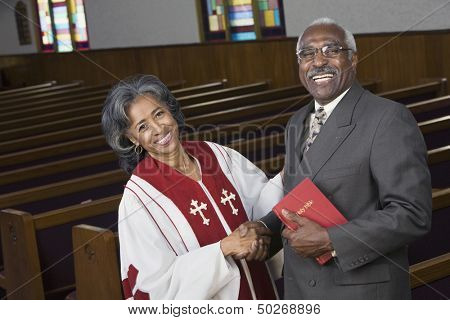 Female Reverend shaking hands with parishioner