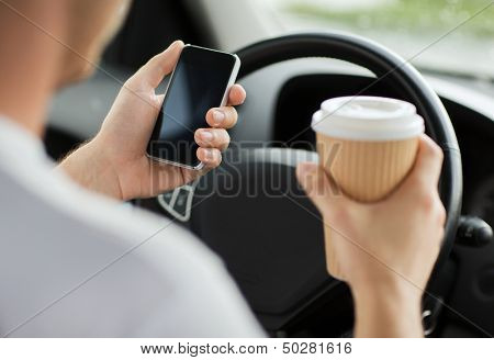 transportation and vehicle concept - man drinking coffee and using phone while driving the car