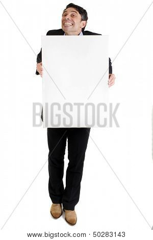 Businessman with a cheesy toothy grin of insincerity and obsequiousness holding a blank white sign with copyspace for your text or advertising, full length isolated on white