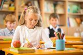 Little schoolgirl sitting behind school desk during lesson in school poster