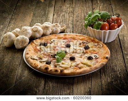 pizza capricciosa on dish over wood background poster
