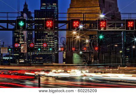 Light trails and road signs on Sydney Harbour Bridge at dusk
