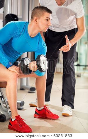 Young man exercising under supervision personal trainer poster