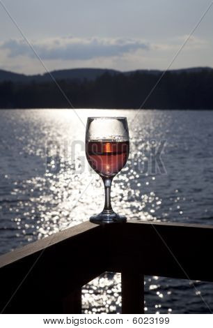 Glass of red wine on a deck overlooking a lake