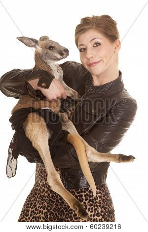 a woman in her leather jacket with a small smile on her face holding on to her pet kangaroo. poster