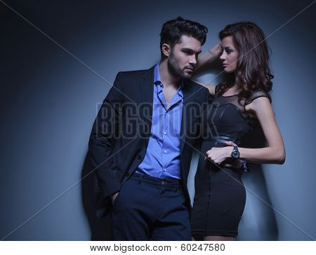 portrait of a young fashion man holding a beautiful woman while looking away with his hand in his pocket. on a dark blue background