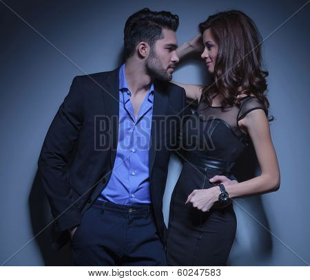 portrait of a young fashion woman being held by a handsome man while they are looking into each other's eyes. on a dark blue background
