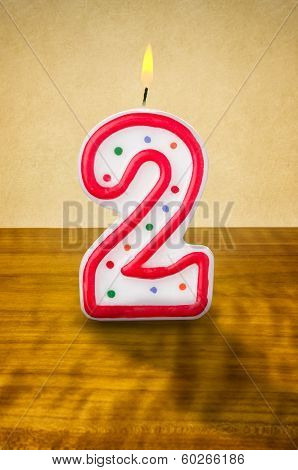 Burning birthday candle number 2 on a wooden background
