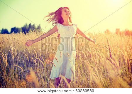 Beauty Girl Outdoors enjoying nature. Beautiful Teenage Model girl in white dress running on the Spring Field, Sun Light. Glow Sun. Free Happy Woman. Toned in warm colors.  poster