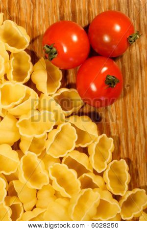 Macaroni and tomato on wooden background