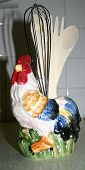 this is a ceramic rooster that holds kitchen utensils. poster