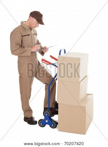 Delivery Man Writing On Clipboard By Cart And Cardboard Boxes