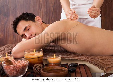Relaxed Man Receiving Shoulder Massage In Spa