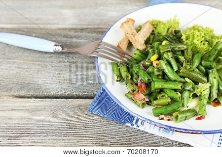 Salad with green beans, ham and  corn on plate, on color wooden background