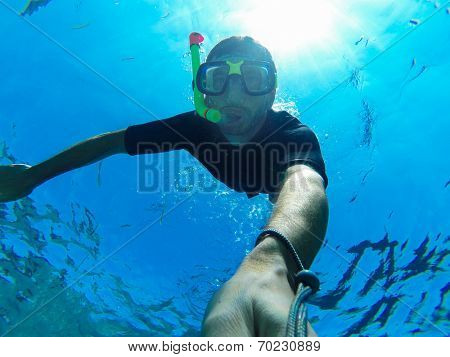 Freediving: self-portrait of a male freediver while descending under the sea.