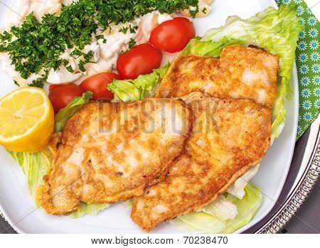 Baked plaice fillet with potato salad on a plate with tomato and salad decoration