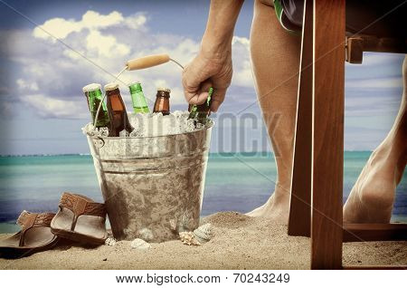Closeup of a man sitting in a wooden chair at the beach reaching into a bucket filled with ice and beer bottles. Horizontal forma