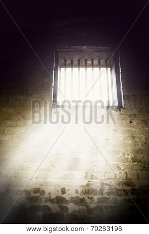 Interior of prison cell with light shining through the window