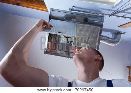 Handyman Fixing Kitchen Wall Hood