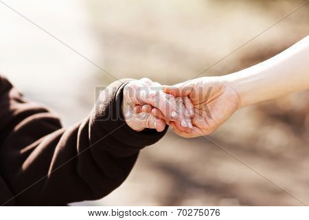 Senior Woman Holding Hands With Young Caretaker
