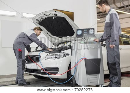 Male automobile mechanics examining car in repair shop