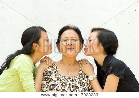 Two Granddaughter Kiss Their Old Grandmother