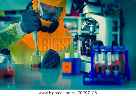 Laboratory test of Ebola virus. Scientist takes blood out test tube in  pipette microscope studies in biological samples.