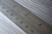 metal ruler on brushed abstract metal background poster