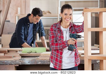 Portrait of happy female carpenter drilling wood while colleague working in background at workshop