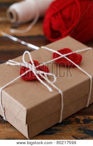 Saint Valentine decoration: handmade crochet red heart for gift paper box. Selective focus poster