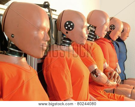 Five test dummies with orange suits in a row. poster