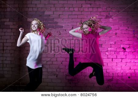 Teenage Girl Jump Against Purple Brick Wall Background