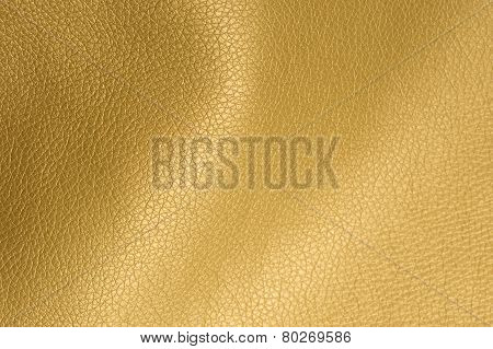 A close-up of golden glossy artificial leather background texture poster
