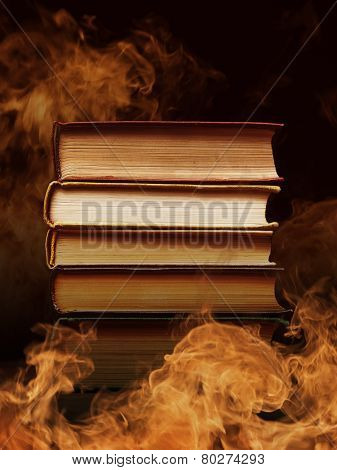 Pile of hardcover books surrounded with swirling tendrils smoke or vapor in a darkened vintage style room conceptual of magic, fire, spirituality or alchemy poster