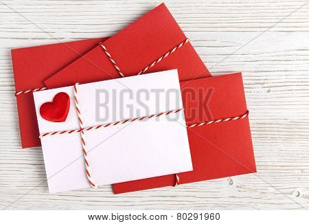 Envelope Mail with Red Heart and Ribbon over White Wooden Background. Valentine Day Card Love or Wedding Greeting Concept.