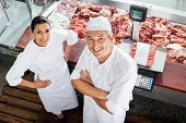 High angle portrait of confident male and female butchers standing at butchery counter poster