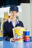 Portrait of happy female worker with popcorn and drink at concession counter in cinema poster