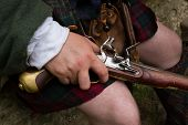 Close up of a flintlock pistol being held naturally resting on knee of a jacobite wearing a kilt poster