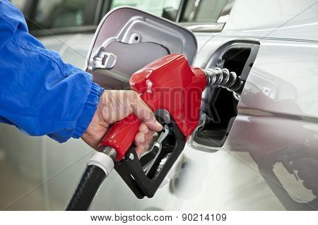 Red Nozzle Filling Up Tank With Gas