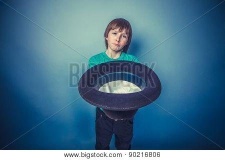 European-looking  boy  of ten years beggar holding hat in hand o