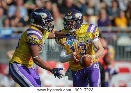 VIENNA, AUSTRIA - APRIL 27, 2014: QB Alexander Thury (#13 Vikings) hands off the ball to RB Anthony Stevenson (#25 Vikings).