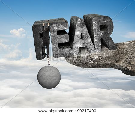 Man Shackled By Ball Hanging Fear Word Edge Cliff Cloudscape