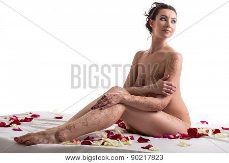 Mehandi. Brunette posing nude in bed with petals