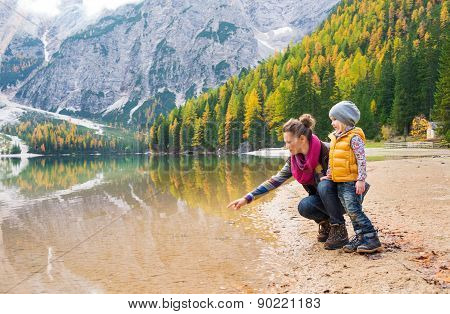 Mother Pointing And Kneeling Next To Daughter At Lake Bries