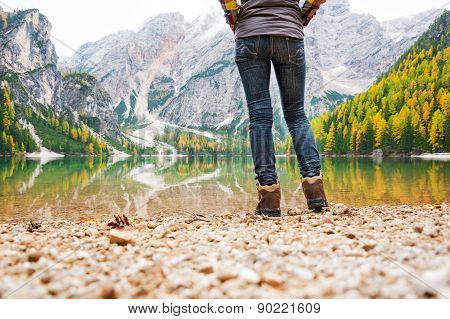 Study of the bottom half. A woman hiker stands at the edge of Lake Bries. In the foreground a pebbly beach. In the background the lake is a mirror reflection of the mountains and autumn colours. poster
