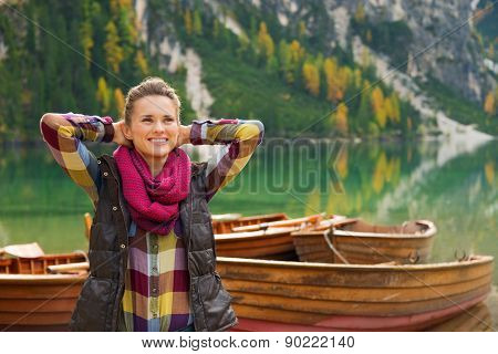 Wearing outdoor gear a brunette woman hiker relaxes hands behind her head. She is happy and content. In the background wooden boats float on the water. Autumn colours and trees are reflecting off the still water. poster