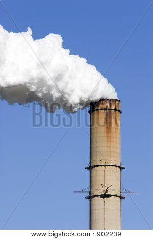 white smoke billowing from the smokestack of a powerplant. against a clear blue sky. poster